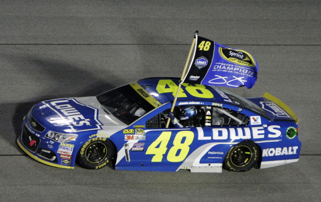 Jimmie Johnson hold his flag as he does the victory lap after wining the NASCAR Sprint Cup auto race and season title Sunday, Nov. 20, 2016, in Homestead, Fla. (AP Photo/Darryl Graham)
